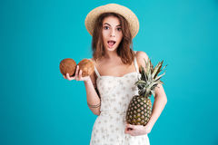 Girl in summer clothes holding two coconuts and pineapple Stock Images
