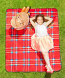 Girl in summer clothes laying on picnic blanket Royalty Free Stock Image