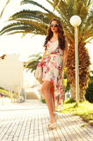 Girl in summer dress. Beautiful girl walking in summer dress against palms Stock Photography