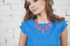 Girl in summer  dress demonstrates mauve necklace Royalty Free Stock Image