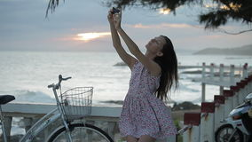 Girl in summer dress is making selfie on the embankment near a beach at sunset. stock footage