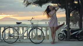Girl in summer dress is making selfie on the embankment near a beach at sunset. stock video