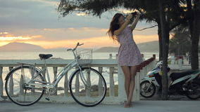 Girl in summer dress is making selfie on the embankment near a beach at sunset. stock video footage