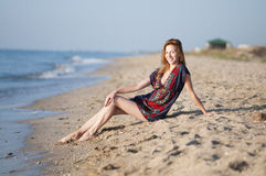 girl in a summer dress sitting on the beach Royalty Free Stock Images