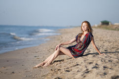 girl in a summer dress sitting on the beach Stock Photos