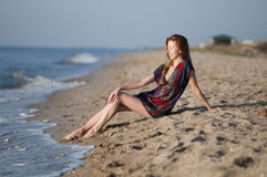 girl in a summer dress sitting on the beach Stock Image