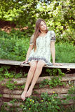 Girl in a summer dress sitting and relaxing Stock Images