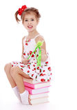 Girl in summer dress sitting on a stack of books Royalty Free Stock Image