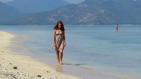 Girl in summer dress walking along beautiful beach stock video footage