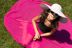Girl in summer fashion. Young girl in white hat and sunglasses outdoor Stock Image