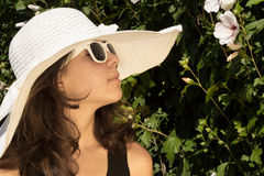 Girl in summer fashion. Young girl in white hat and sunglasses outdoor with flower Royalty Free Stock Image