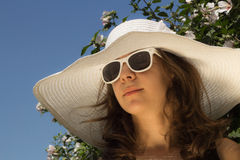 Girl in summer fashion. Young girl in white hat and sunglasses outdoor with flower and blue sky Stock Photography