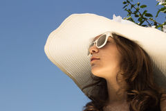 Girl in summer fashion. Young girl in white hat and sunglasses outdoor with flower and blue sky Royalty Free Stock Image