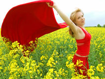Girl in summer field. A beautiful teen girl in red dress in yellow flowers summer field stock photography