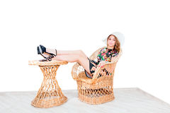 Girl in summer hat isolated on wicker chair Stock Image