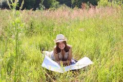 The girl on summer meadow with topographic map Royalty Free Stock Image
