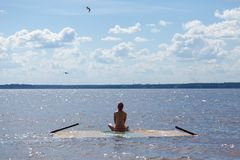 А meditating girl on the water royalty free stock photography