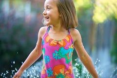 Girl Summer Splash. A little grade schooler girl splashing in water stock photos