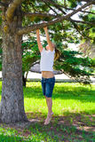Girl in summer try to jump on tree Royalty Free Stock Photography