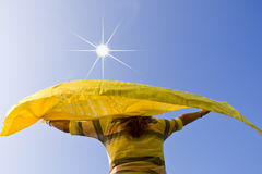 Girl in the sun. Girl who holds a scarf blowing in the wind Royalty Free Stock Images
