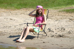 Girl in sun-chair. Cute summer girl watching the action on the beach Stock Photography