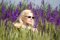 Girl in sun glasses. Beautiful blonde girl in sun glasses in the field of violet flowers royalty free stock images