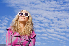 Girl in sun glasses. Beautiful girl in big sun glasses against blue sky Royalty Free Stock Photos