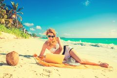 Girl with sun glasses and notebook on the tropical beach Royalty Free Stock Image
