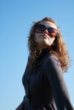 Girl in sun glasses poses against the blue sky Stock Images