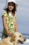 Girl (6-8) in sun hat standing on beach with dog, smiling, side view, portrait Stock Images