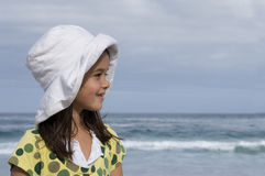 Girl (6-8) in sun hat standing on beach, smiling, profile, sea in background Royalty Free Stock Photography