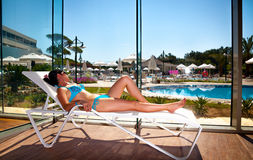 Girl on a sun lounger Stock Images