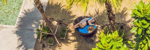Girl in sun loungers among palm trees near the swimming pool BANNER, long format royalty free stock photos