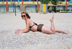 The girl sunbathes on a beach. The girl at sea of Azov sunbathes on a beach in sun glasses Royalty Free Stock Photos