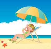 Girl sunbathes lying on a sun lounger on the beach Royalty Free Stock Photography