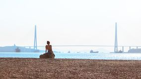 The girl sunbathes in the morning sun on the background of the Russian bridge on the Russky island across the East Bosphorus in. The Far Eastern city of royalty free stock image