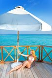 The girl sunbathes on a tropical beach. Young woman tans on a water villa terrace , Maldives royalty free stock photography