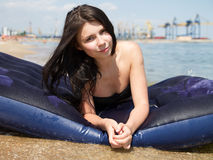 Girl sunbathing on air mattress in sea Royalty Free Stock Photography