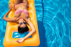 Girl sunbathing on air mattress Stock Photos