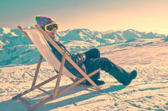 Girl sunbathing in a deckchair on the side of a ski slope, vintage Stock Image