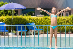 Girl sunbathing on the edge of the pool. Raised his hands up Royalty Free Stock Image
