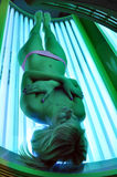 Girl sunbathing in a green solarium. Beautiful blonde girl sunbathing in a green solarium Royalty Free Stock Photo