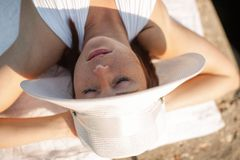 Girl sunbathing with hands behind head and eyes closed. Girl sunbathing with hands behind head. Female person in white hat and white swimwear lying on concrete royalty free stock photos