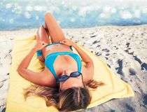 Girl sunbathing on the beach on towel. summertime concept royalty free stock photo