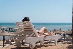 Girl sunbathing on a lounger on the beach. In the background a pier is visible Royalty Free Stock Photos