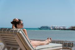 Girl sunbathing on a lounger on the beach. In the background a pier and yacht are visible Stock Photos
