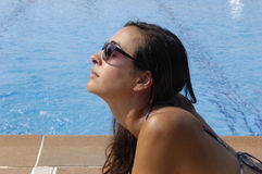 A girl sunbathing. Near a swimming pool Royalty Free Stock Image
