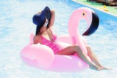 Girl sunbathing on a pink flamingo in the pool. Gorgeous girl sunbathing on a pink flamingo in the pool and her face is covered with a sun hat. Pool party Royalty Free Stock Photo