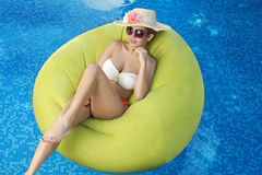 Girl sunbathing in the pool. luxurious resort concept.  Royalty Free Stock Image