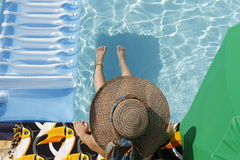 Girl sunbathing in the pool. Girl sitting by the edge of the pool, wearing a hat Stock Image